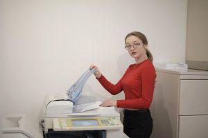 serious-female-office-worker-using-printer-in-workplace-3831873-1.jpg